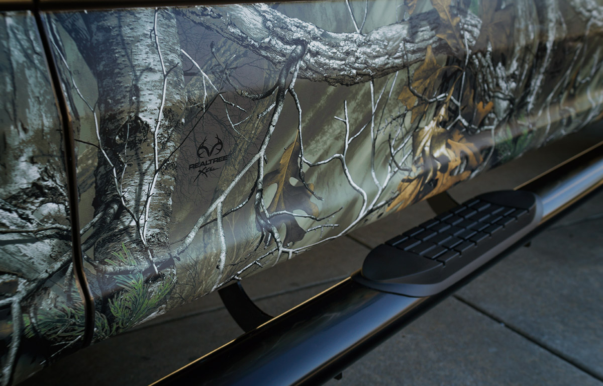 RealTree Camo Vinyl Wrap package on a 2016 Ford F150 with camo wrapped lower door panels close up